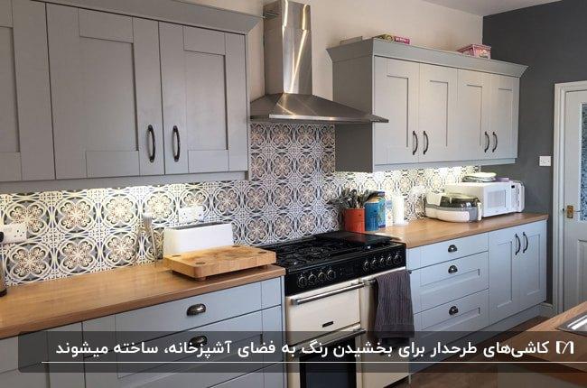 آشپزخانه ای با کابینت های طوسی و صفحه رویی چوبی به همراه کاشی بین کابینتی طرحدار