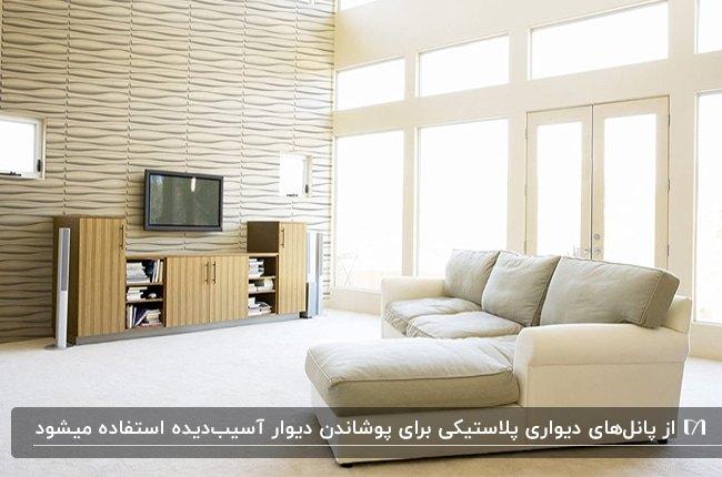 دکوراسیون داخلی اتاق پذیرایی با دیوارپوش پلاستیکی کرم رنگ و یک مبل ال شکل کرم و طوسی مقابل تلویزیون