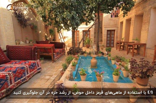 حیاط یک ملک سنتی با دیوارهای آجری قهوه ای، تخت های چوبی با فرش قرمز و حوض مستطیلی