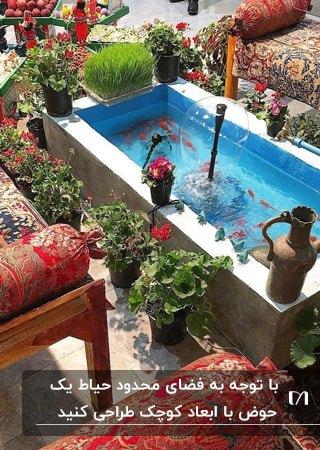 حوض مستطیلی کوچک با فواره و گلدان های شمعدانی اطرافش