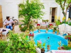 حیاطی قدیمی و سنتی با یک حوض دایره ای آبی وسط حیاط و گلدان ها و درخت های سبز اطرافش