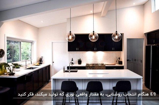 آشپزخانه ای با نورپردازی های نقطه ای و روشنایی های آویز بالای جزیره