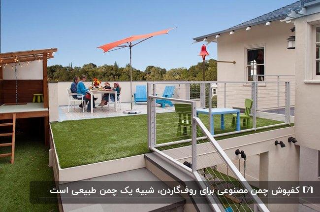 روفگاردنی با میز و صندلی های سفید، سایبان چتری نارنجی، دو صندلی کنار استخری آبی و کفپوش چمن مصنوعی