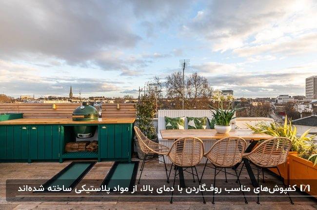 روفگاردنی با میز غذاخوری چوبی و صندلی های حصیری با پایه فلزی مشکی، کابینت سبز و کفپوش قهوه ای