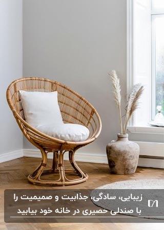 تصویر یک صندلی حصیری گرد و گود با تشکچه و کوسن سفید کنار گلدان با دو خوشه گندم کنار پنجره