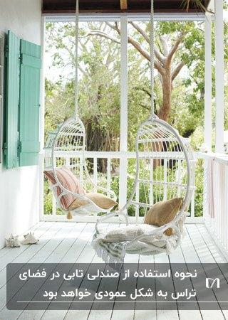 تراس خانه ای با حفاظ سفید و کفپوش چوبی سفید رنگ با دو صندلی تابی سفید