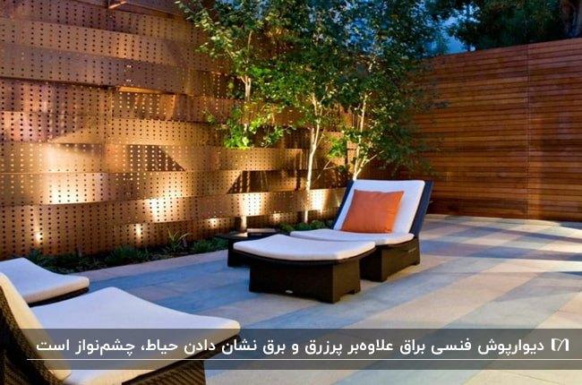 دیوارپوش فنسی براق مسی رنگ در حیاطی با دو تخت کنار استخر حصیری قهوه ای با تکشچه سفید و کوسن نارنجی