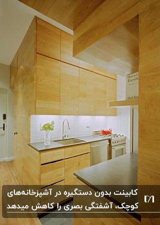آشپزخانه ای کوچک و کم جا با کابینت های چوبی و درب کابینت ساده و بدون دستگیره