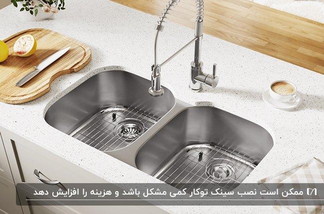 سینک دو لگنه استیل با یک تخته چوبی در آشپزخانه ای با کابینت های سفید رنگ