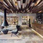 طراحی لابی یک آپارتمان کوچک با طراحی چوبی سقف ، شومینه آویز و گودال آتش و قفسه های دکوری دیواری