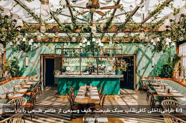 دکوراسیون داخلی کافیشاپ کوچکی به سبک طبیعت با میز و صندلی های چوبی و گل ها و گیاهان روی سقف