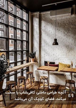 دکوراسیون داخلی کافیشاپ کوچکی با دیوار سفید آجری و میزهای مربعی و چهارپایه های گرد چوبی