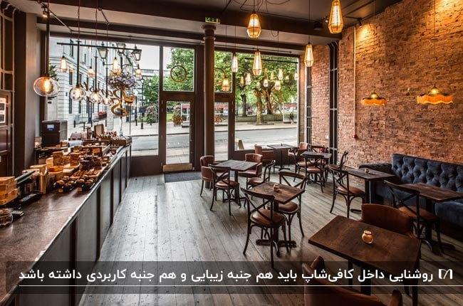 دکوراسیون داخلی کافیشاپ کوچکی با دیوارهای آجری و میز و صندلی های قهوه ای با چراغ های آویز