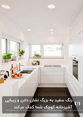 آشپزخانه کوچک و باریکی با دیوار ، کابینت ها و صفحه رویی کابینت سفید