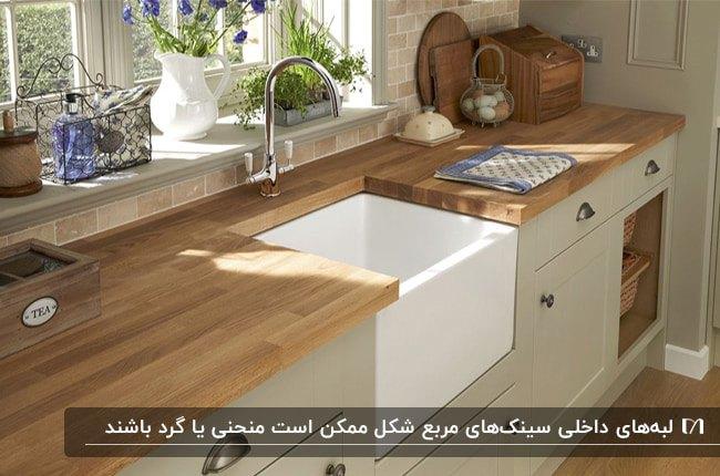 سینک مربع شکل سفید در آشپزخانه با کابینت کرم و قهوه ای