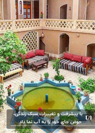 حیاط خانه دو طبقه ای با دیوارهای گلی، تخت های چوبی با روکش های زرشکی و حوض چند ضلعی