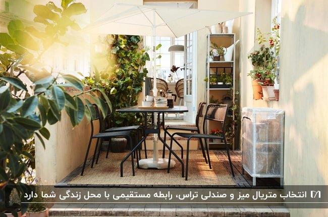 میز و صندلی های مشکی فلزی با سایبان چتری سفید رنگ در تراس