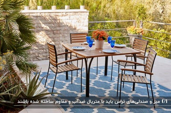 میز و صندلی های چوبی با پایه فلزی مشکی روی فرش طرحدار سفید و آبی در تراس