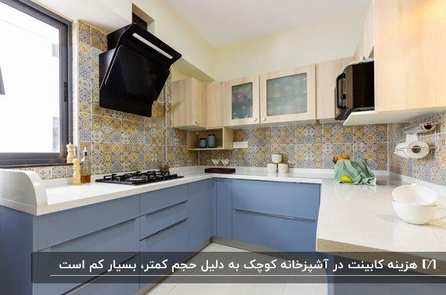 آشپزخانه کم جا با کابینت های کرم و آبی، کاشی بین کابینتی طرحدار و هود مشکی