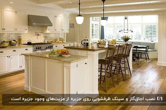 آشپزخانه ای با کفپوش چوبی قهوه ای، کابینت ها و جزیره سفید و چهارپایه های چوبی قهوه ای تیره کانتر