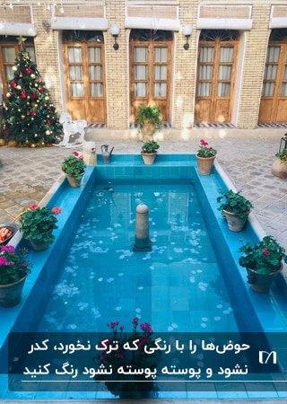 حوض آبی رنگ مستطیلی با گلدان های گل دورتا دورش در حیاط خانه ای سنتی با درب های چوبی
