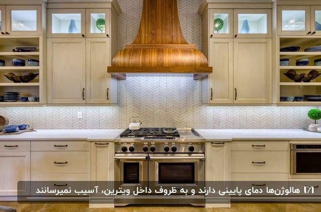 آشپزخانه ای با کابینت یکطرفه سفید رنگ و ویترین هایی با درب شیشه ای و هالوژن های داخلش