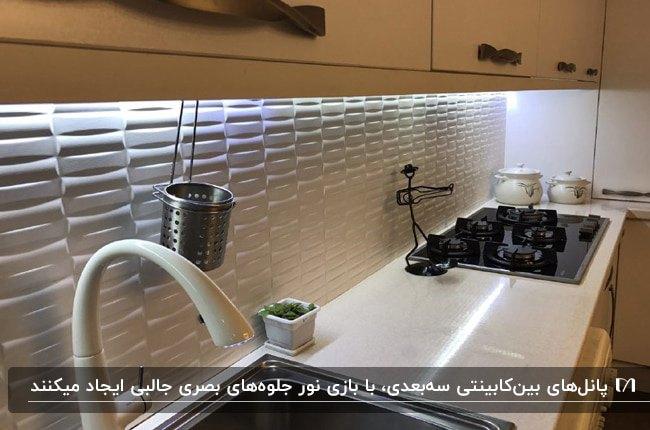 آشپزخانه ای با کابینت های کرم رنگ و پنل بین کابینتی سه بعدی سفید رنگ