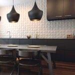 کابینت های مشکی و میزغذاخوری، صندلی و لوستر های زغالی با پنل دیواری سه بعدی سفید