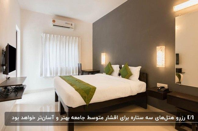 اتاق خواب هتلی سه ستاره با تهت دو نفره و روتختی و کوسن های سبز، دیوار خاکستری، میز آرایش و آینه، تلویزیون و دو دیوارکوب