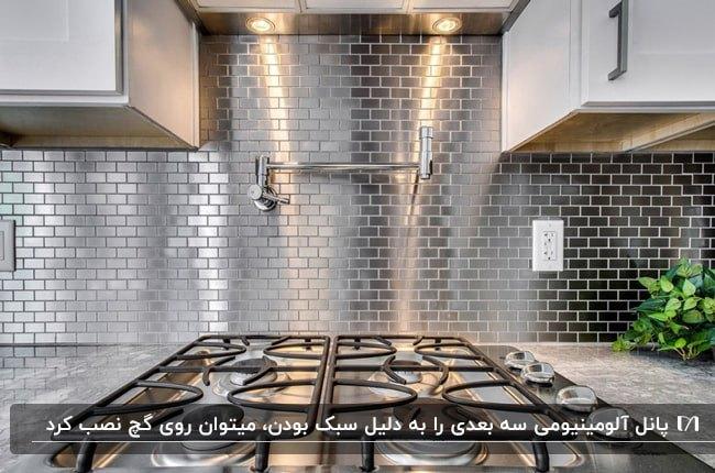 کابینت های سفید و اجاق گاز نقره و مشکی در آشپزخانه ای با پنل دیواری سه بعدی آلومینیومی براق