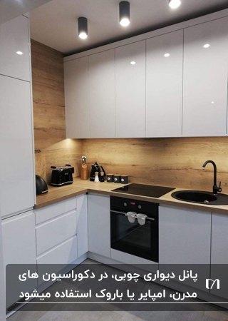 کابینت های سفید براق و پنل دیواری سه بعدی چوبی در آشپزخانه ای مدرن