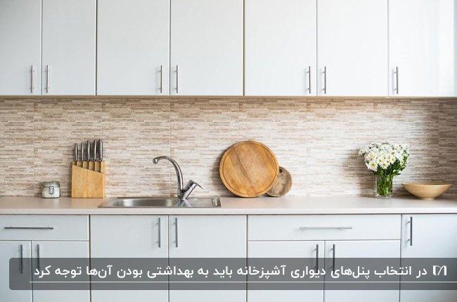 آشپزخانه ای با کابینت های طوسی خیلی روشن و دیوارپوش بین کابینت سنگی با تم کرم و قهوه ای