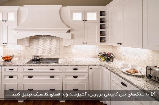 آشپزخانه مدرنی با کابینت های سفید و دستگیره های مشکی به همراه دیوارپوش بین کابینتی سنگ تراورتن سفید