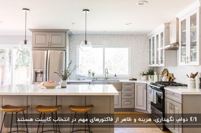 تصویر یک آشپزخانه با کابینت های کرم و سفید و چهارپایه چوبی و فلزی