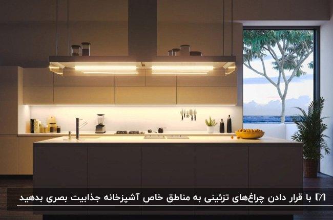 آشپزخانه ای با کابینت ها و جزیره سفید با نورپردازی های زیر کابینت و چراغ های هود