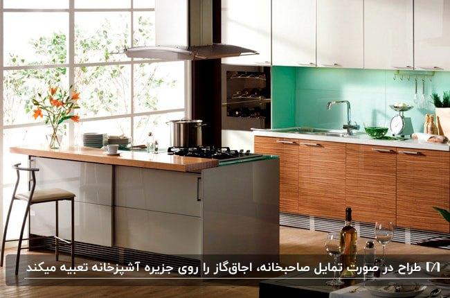 آشپزخانه ای با کابینت های ترکیبی چوبی و سفید و طوسی و جزیره و اجاق گاز و هود کنار پنجره