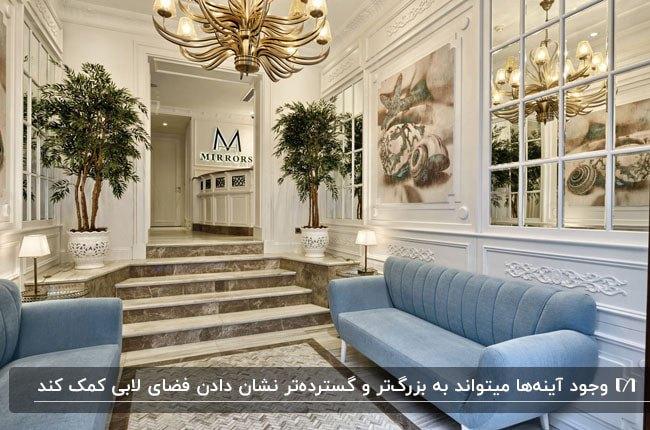 طراحی لابی یک آپارتمان کوچک با مبلمان آبی آسمانی و آینه کاری های مربع مربع روی دیوار