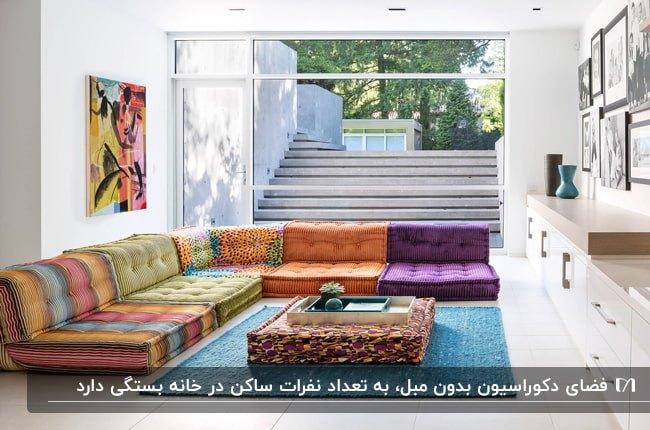 نشیمن بدون مبل با تشکچههای رنگی، فرش آبی و میز عسلی مربعی بدون پایه