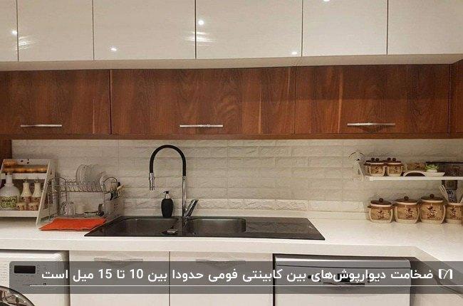 آشپرخانه ای با کابینت های ترکیبی سفید براق و چوب رگه دار و پنل های بین کابینتی فومی سفید رنگ