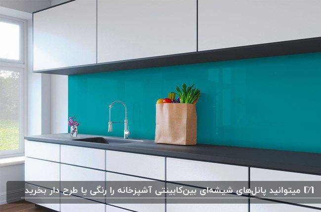 آشپزخانه ای با کابینت های سفید، صفحه روی کابینت مشکی و دیوارپوش بین کابینت شیشه ای آبی