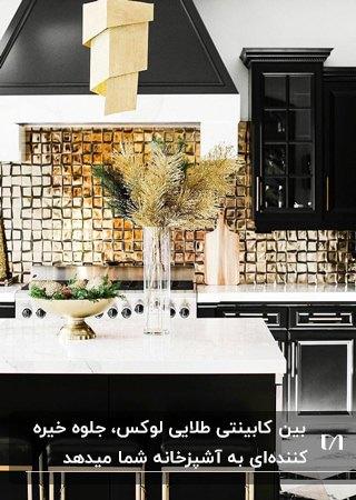آشپزخانه ای با کابینت های براق مشکی، صفحه رویی کابینت سفید و پانل های بین کابینتی طلایی