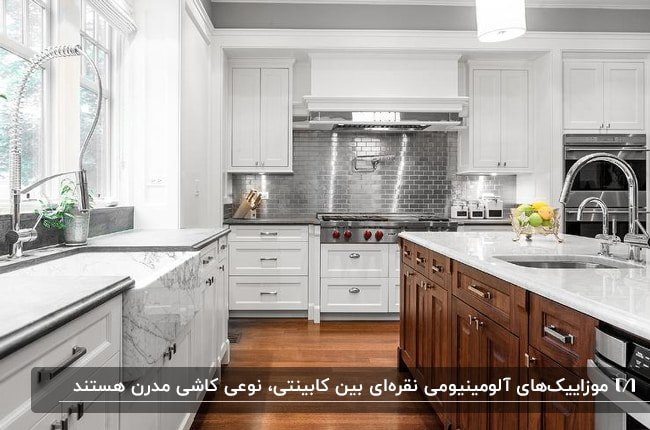 آشپزخانه ای با کابینت های سفید، جزیره چوبی، صفحه رویی کابینت ها و جیزره سفید با دیوارپوش فلزی بین کابینت نقره ای
