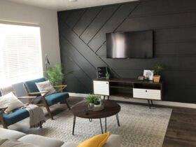 دکوراسیون داخلی اتاق پذیرایی با دیوارپوش برجسته مشکی با مبلمان کرم و آبی و میز عسلی گرد چوبی تیره