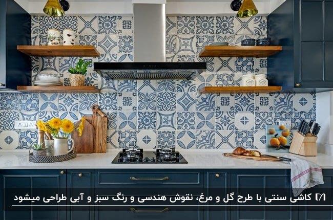 آشپزخانه ای با کابینت های سرمه ای با صفحه رویی سفید به همراه کاشی های طرحدار سنتی سفید و آبی