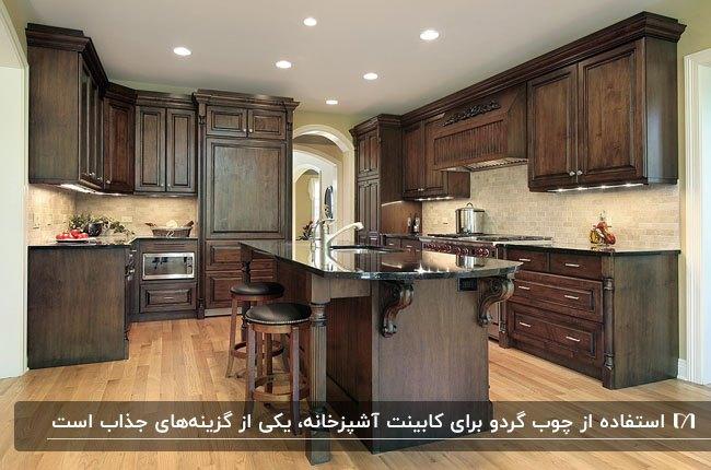 آشپزخانه بزرگی با کفپوش چوبی روشن و کابینت و جزیره از چوب گردو قهوه ای تیره