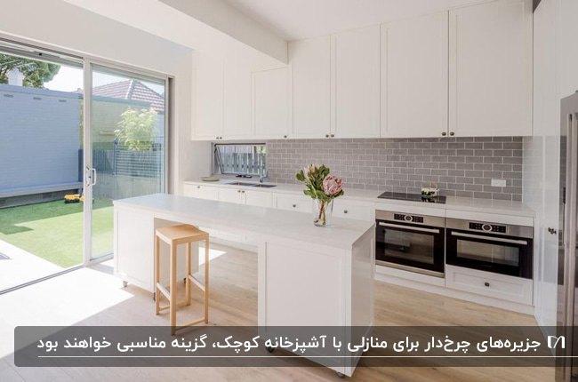 آشپزخانه ای با کابینت ها و جزیره چرخدار سفید کنار دیوار شیشه ای حیاط خلوت