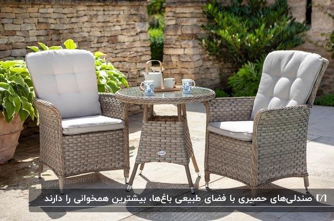 تصویر دو صندلی و میز عسلی گرد حصیری مصنوعی در فضای باغ