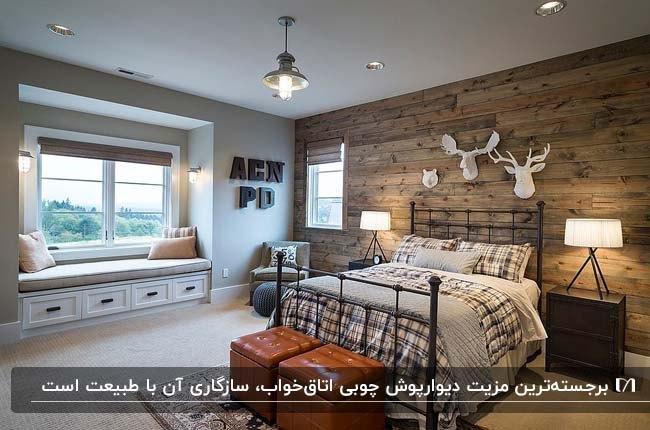 دکوراسیون اتاق خوابی با تخت فلزی، دو پاف چرم، دیوار چوبی و مجسمههای گوزن
