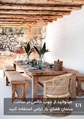 میز و صندلی ها و نیمکت چوبی قهوه ای در تراس با اکسسوری هایی روی میز