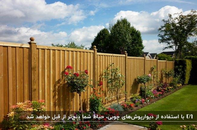 تصویری از دیوارپوش چوبی حیاطی با گل های صورتی و زمین چمن کاری شده